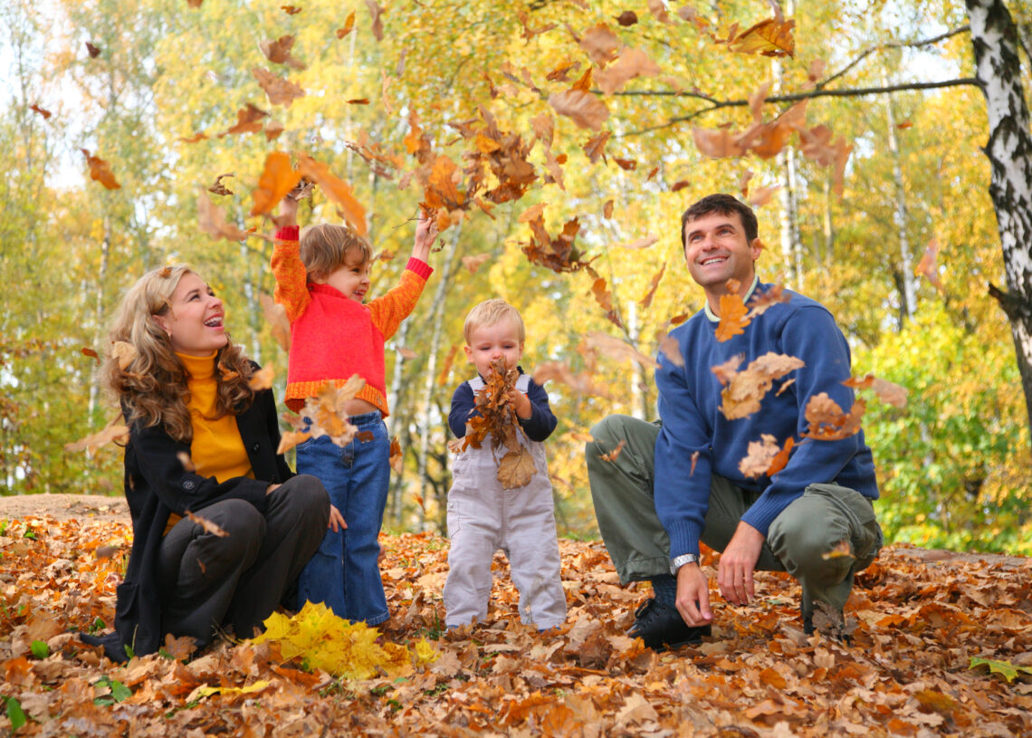 family throw autumnal leaves